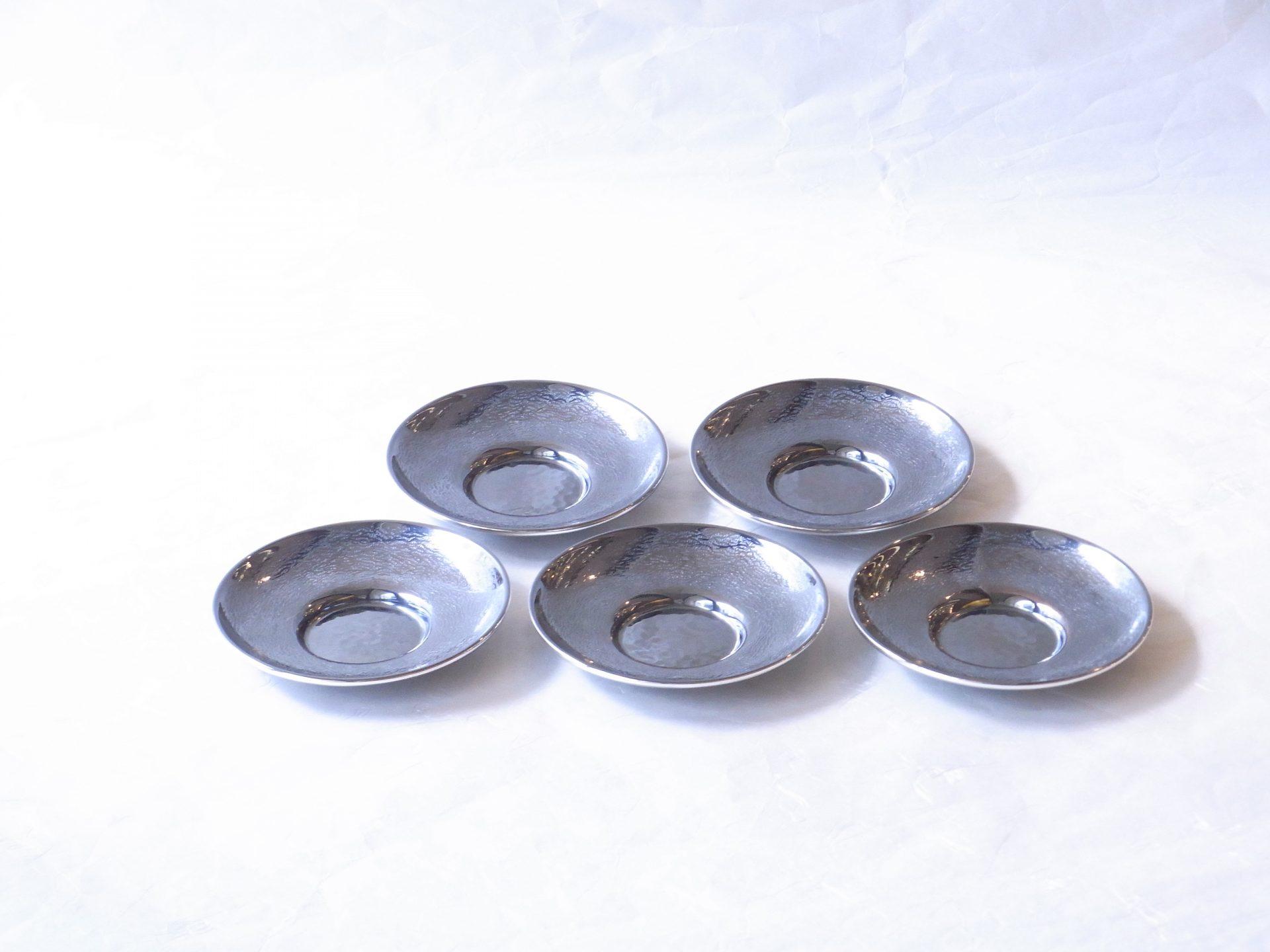 金属製品 高岡銅器 いぶし銀 仕上げ 茶托 5客揃 さざ波 鎚起銅器 鎚目模様 小さな波 細かく 不規則 熟練の職人 豊かな経験 細心の注意を払い 厳重な品質管理 高級品 表面硬化 変色しにくい 銀メッキ 銀特有 やわらかさ 工芸美術品 味わい深さ 乾拭き いい光沢が出てくる ガラスの湯呑 相性がいい 現代風 スタイリッシュな湯呑み マッチ 組み合わせ次第 お洒落 割れない 劣化も少ない 永く使える 日本製 陶器 磁器 陶磁器 漆器 茶道具 華道具 贈り物 ギフト 記念品 引出物 法要 お返し 専門店 リアル店舗 茶の湯 茶道 裏千家 表千家 茶会 月釜 抹茶 高品質 安らぎ いやし よりおいしく 安心 機能的 長持ち 人気 おすすめ 高機能 ネット通販 ネットショップ セレクトショップ 欲しい 購入 買う 買い物 岐阜県 岐阜市 美殿町 小林漆陶 特別な 選び抜かれた 品質重視 使いやすい 格安 老舗 誕生日 結婚 出産 入学 退職 母の日 父の日 敬老の日 クリスマス プレゼント 叙勲 長寿 新築 お祝い 御礼 内祝い 外国土産 海外みやげ 実店舗 創業100年以上 使うと分かる 職人技 日本一の品揃え 日本一の在庫数 専門店 専門知識 数万点の在庫 百貨店(高島屋 三越 伊勢丹 松坂屋 大丸)にない 手作り お洒落 高級品 希少価値 上質な器 伝統工芸品 コスパ お値打ち お買い得 堅牢 飽きない 永く使える お気に入り 国産 料理が映える 満足感 豊かな食生活 豊かな食文化 こだわりの器 日本文化 他にない ここにしかない オリジナル 独自の 個性的 ここでしか買えない 超レアもの 一品もの 現品限り 入手困難 いい器 匠の技 美しい 実用的 外人が喜ぶ店 外人が珍しがる店 外人がうれしい店 日本各地の一級品を売る店 日本全国の器を売る店 本当にいいもの コスパ高い 一流品 修理 選りすぐりの逸品 周年記念 永年勤続表彰 退職記念 卒業記念 日本土産 岐阜土産 岐阜のおみやげ 岐阜の特産品 料理を引き立てる器 高級店 一流店 岐阜で一番 東海で一番 中部で一番 日本で一番 おしゃれな店 地域一番店 実店舗 陶磁器 磁器 華道具 ガラス器 明治42年創業 有田焼 清水焼 美濃焼 赤津焼 万古焼 常滑焼 九谷焼 唐津焼 萩焼 信楽焼 万古焼 砥部焼 備前焼 丹波焼 山中塗 春慶塗 讃岐塗 越前塗 輪島塗 紀州塗 会津塗 小田原木工 桜皮細工 秋田杉 駿河竹細工 七宝焼 南部鉄器 錫製品 江戸切子 津軽びいどろ