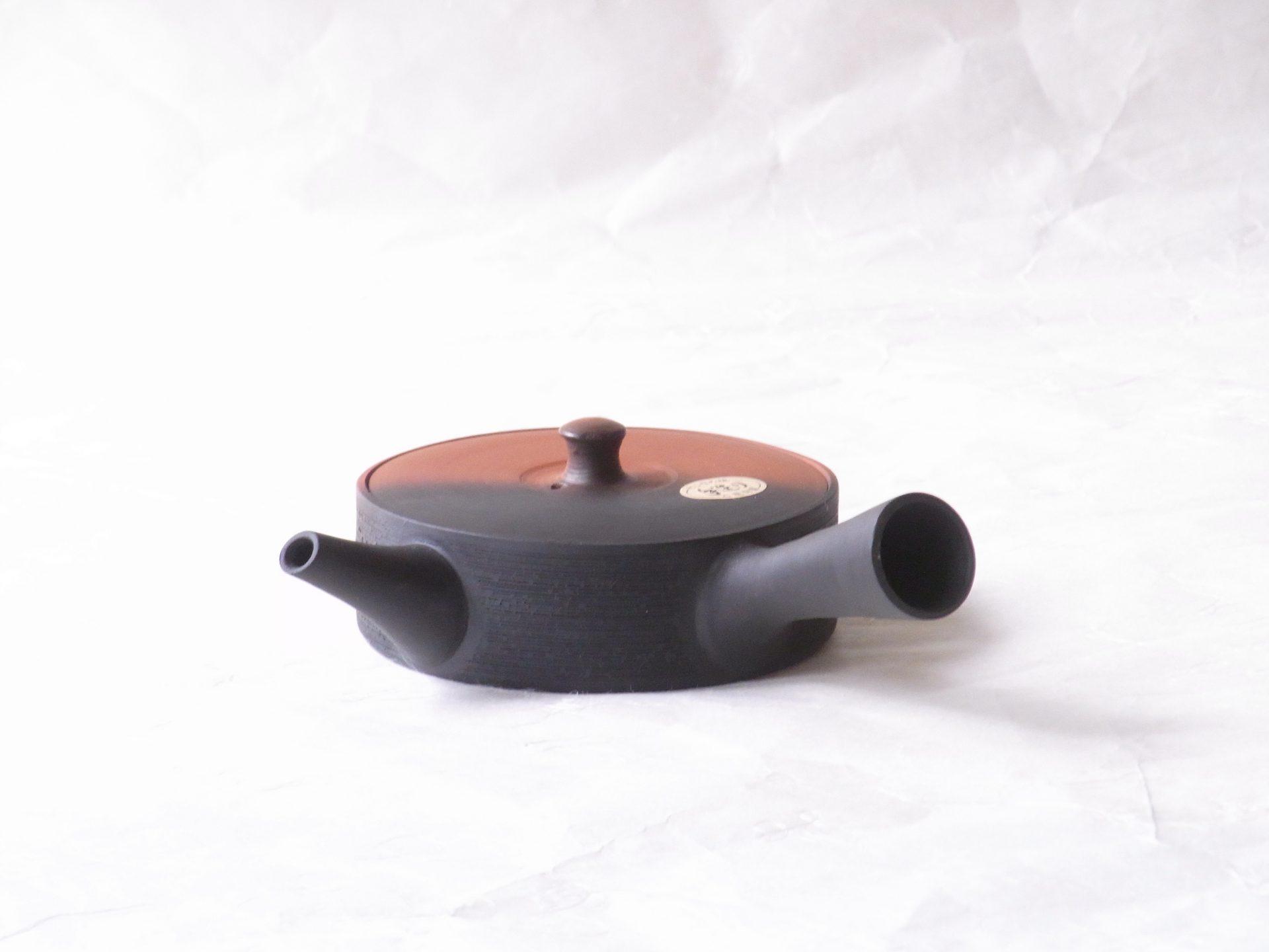 陶磁器 常滑焼 手づくり 究極の平型急須 朱泥・黒ツートン 窯変 松皮 一人用 140cc お茶の味を最大限に引き出す 低く平たく作られた 究極の形 茶葉が早く開く 広がりも良い よりおいしく お茶を抽出できる 水出し冷茶にも使える 一人用 飲み切り 一煎一煎おいしいお茶 陶器製 手づくり茶こし 熟練の職人技 口径と胴径が同じ 急須の内側が洗いやすい 衛生的 朱泥 黒窯変 朱と黒窯変のツートン 朱と黒両方楽しむ 松皮 松の樹皮のような細かい筋 横方向に無数 細部にも手間 蓋きっちり 注ぎ口 液だれしにくい 片手でも、親指で蓋を押さえながら 機能的 究極の急須 日本製 陶器 磁器 陶磁器 漆器 茶道具 華道具 贈り物 ギフト 記念品 引出物 法要 お返し 専門店 リアル店舗 茶の湯 茶道 裏千家 表千家 茶会 月釜 抹茶 高品質 安らぎ いやし よりおいしく 安心 機能的 長持ち 人気 おすすめ 高機能 ネット通販 ネットショップ セレクトショップ 欲しい 購入 買う 買い物 岐阜県 岐阜市 美殿町 小林漆陶 特別な 選び抜かれた 品質重視 使いやすい 格安 老舗 誕生日 結婚 出産 入学 退職 母の日 父の日 敬老の日 クリスマス プレゼント 叙勲 長寿 新築 お祝い 御礼 内祝い 外国土産 海外みやげ 実店舗 創業100年以上 使うと分かる 職人技 日本一の品揃え 日本一の在庫数 専門店 専門知識 数万点の在庫 百貨店(高島屋 三越 伊勢丹 松坂屋 大丸)にない 手作り お洒落 高級品 希少価値 上質な器 伝統工芸品 コスパ お値打ち お買い得 堅牢 飽きない 永く使える お気に入り 国産 料理が映える 満足感 豊かな食生活 豊かな食文化 こだわりの器 日本文化 他にない ここにしかない オリジナル 独自の 個性的 ここでしか買えない 超レアもの 一品もの 現品限り 入手困難 いい器 匠の技 美しい 実用的 外人が喜ぶ店 外人が珍しがる店 外人がうれしい店 日本各地の一級品を売る店 日本全国の器を売る店 本当にいいもの コスパ高い 一流品 修理 選りすぐりの逸品 周年記念 永年勤続表彰 退職記念 卒業記念 日本土産 岐阜土産 岐阜のおみやげ 岐阜の特産品 料理を引き立てる器 高級店 一流店 岐阜で一番 東海で一番 中部で一番 日本で一番 おしゃれな店 地域一番店 実店舗 陶磁器 磁器 華道具 ガラス器 明治42年創業